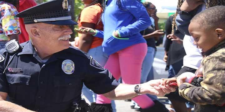 Sumter Police Officer handing a little kid halloween candy