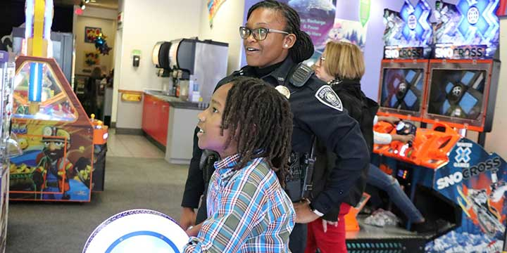 Sumter Police Officer playing in arcade with a kid