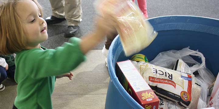 Small child donating to food drive