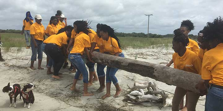 Image of Youth Corps members lifting a large log